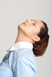 Expectation. A young woman facing upwards with closed eyes in a business shirt Stock Image