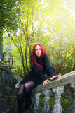 Expectation. Girl in black dress with red hair sitting in a park on the old parapet and stares at the top of the sun Royalty Free Stock Photos