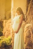 Expectation and happiness. Pregnant woman standing next to haystack stock image