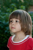 In expectation of a miracle. Portrait of the little girl in red, looking forward against foliage Royalty Free Stock Image