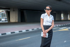 Expectation of success. Confident arabic businesswoman standing. In the street in formal attire. Businessman standing near skyscrapers in Dubai downtown in Royalty Free Stock Photography