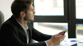 Expected message. Young handsome man using his smartphone with smile while sitting at his working place stock footage