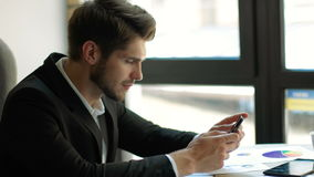 Expected message. Young handsome man using his smartphone with smile while sitting at his working place Royalty Free Stock Image