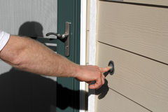 Expecting an Answer. Right hand of a man ringing the front doorbell of a home Royalty Free Stock Photo