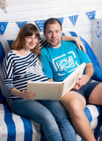 Expecting baby couple sitting on sofa and looking at photo album Royalty Free Stock Image