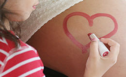 Expecting a brother. Child who is painting a heart on the stomach of its pregnant mother Stock Photo