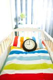 Expecting child. Baby bed and clock as symbol of expectation stock image