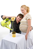 Expecting couple. Conceptual image of an expecting couple watering a young flower in a flower pot Royalty Free Stock Photos