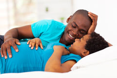 Expecting couple bed. Expecting african american couple lying on bed and chatting Stock Image