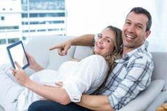 Expecting couple sitting on sofa Stock Photography