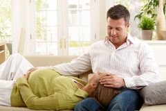 Expecting couple on sofa Stock Photos