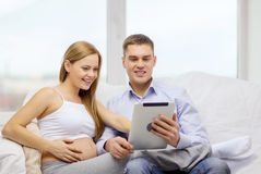 Expecting family with tablet pc computer Stock Photo