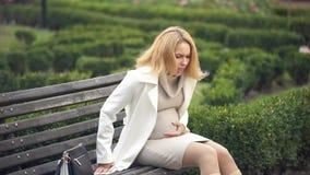 Expecting female feeling sharp abdominal pain, sitting park, miscarriage risk. Stock photo stock photography