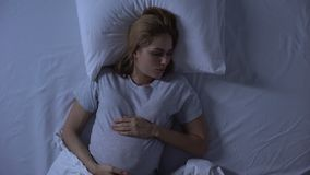 Expecting female tossing in bed at night, pregnancy difficulties, insomnia. Stock footage stock footage