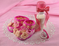 Expecting for a girl. Baby still life with decorated milk bottle and tiny booties for a girl Stock Photography