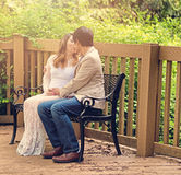 Expecting mom and dad kissing on patio bench outdoors Stock Images