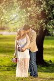Expecting mom and dad kissing under flowering tree Royalty Free Stock Photos