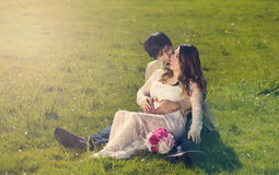 Expecting mom and dad lying in grassy field on bright day Royalty Free Stock Images