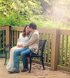 Expecting mom and dad sitting on patio bench outdoors Stock Image