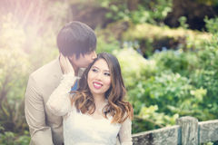 Expecting mom receiving kiss from her husband while outdoors Stock Photos
