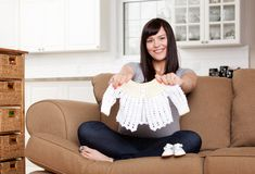 Expecting Mother with Baby Clothes Stock Images
