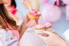 Expecting mother eating cupcake on baby shower party. Expecting mother eating pink cupcake on baby shower party Stock Photos