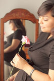 Expecting Mother - It's a Girl!. Image of pregnant hispanic latina woman holding a pink carnation because she is having a baby girl. Mirror in background with Royalty Free Stock Image