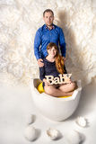 Expecting parents posing at big egg shell with decorative eggs Royalty Free Stock Photo