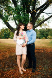 Expecting pregnant happy couple holding blank charcoal board in shape of heart. Stock Photos