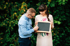 Expecting pregnant happy couple holding a blank charcoal board. Royalty Free Stock Images