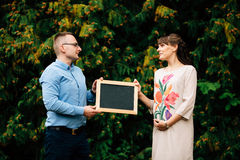 Expecting pregnant happy stylish couple holding a blank charcoal board. Royalty Free Stock Photos