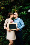Expecting pregnant happy stylish couple holding a blank charcoal board. Royalty Free Stock Images