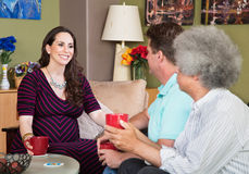 Expecting Surraogate Mother with Friends. Smiling expecting surrogate mother with mature male friends Royalty Free Stock Photos