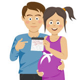 Expecting young parents pointing to calendar. Over white Stock Photography