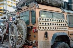 Expedetionlandrover, volledig van modder, met cycli wordt ingepakt die royalty-vrije stock foto