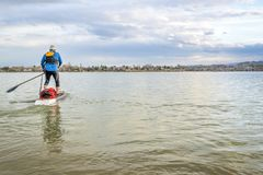 A expedição levanta-se o paddleboard no lago Foto de Stock