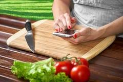 Expediente del cocinero la receta en su smartphone Fotografía de archivo
