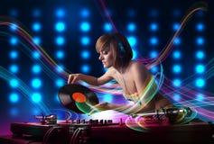 Expedientes de mezcla de la muchacha joven de DJ con las luces coloridas Foto de archivo libre de regalías