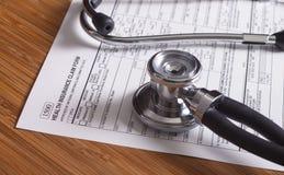 Expedientes, pluma y estetoscopio del seguro médico Foto de archivo libre de regalías