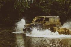 Expeditie offroader De belemmeringsraceauto brandt rubber Mudding van-roading door een gebied van natte modder of klei extreem royalty-vrije stock foto's