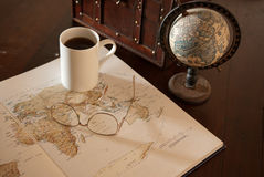 Expedition. Early morning travel planning with map, globe, spectacles and coffee Royalty Free Stock Image