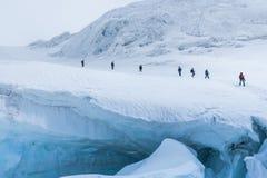 Expedition av fotvandrare i de sn?ig branta bergen arkivfoto