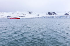 Expedition boat in front of a massive glacier Stock Images