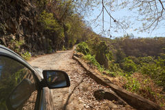 Expedition on car in jungle. In sunny summer day. Side of off road car moving on bad condition road Royalty Free Stock Photography