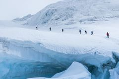 Expedition of hikers in the snowy steep mountains stock photo