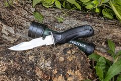Expedition knife and flashlight waterproof on the tree trunk in the forest. Adventure and expedition in the forest with knife for buschcraft and waterproof Royalty Free Stock Image