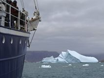 Expedition ship in front of an iceberg. In the arctic sea Stock Images