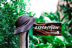 An expedition sign / icon which points the way into the nature. A picture of a sign icon which point the way to go. It is hanging on a wooden stick with a hat royalty free stock images