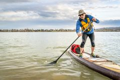 Expedition stand up paddleboard on lake. Senior man on expedition stand up paddleboard with a large waterproof duffel on deck, a lake in Colorado Stock Images
