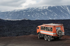 Expedition truck on mountain road on background lava fields and volcanoes Stock Photo